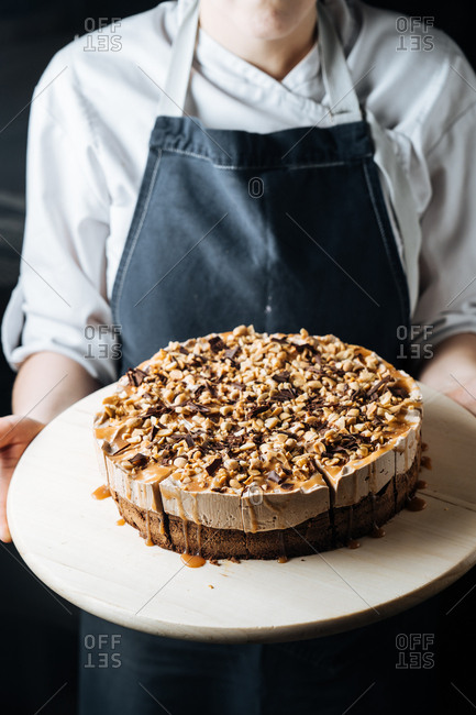 Baker holding a cheesecake with nuts, chocolate, and caramel