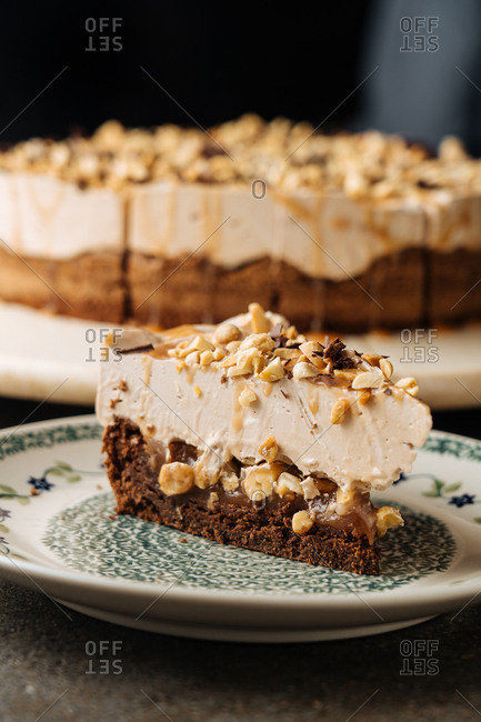 A piece of cheesecake with nuts, chocolate, and caramel