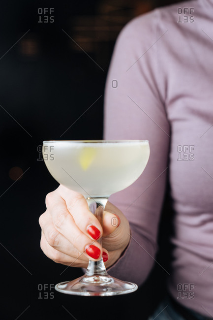 Woman holding a cocktail in a coupe glass