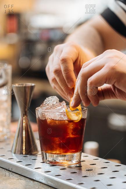 Bartender preparing a cocktail with lemon garnish