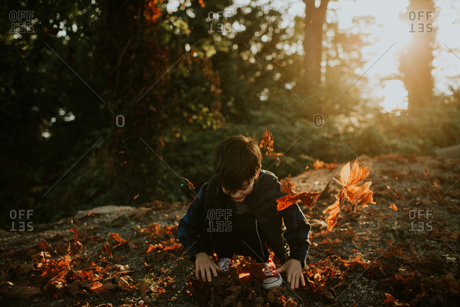 Boy playing with leaves in fall at sunset