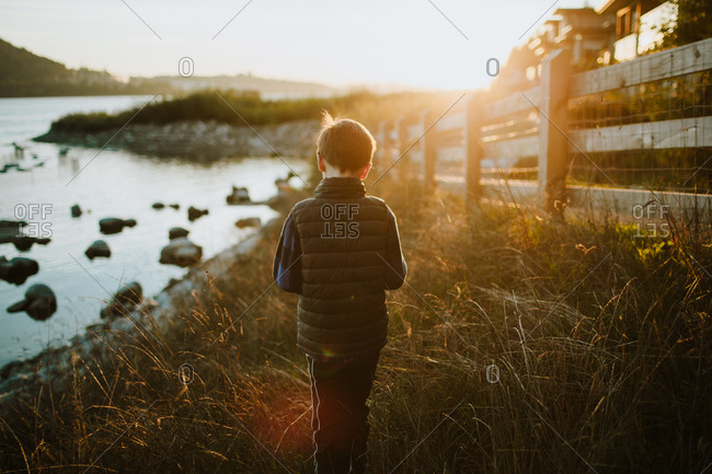 Boy walking by lake at sunset