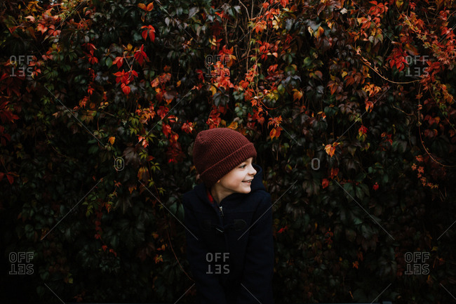 Boy standing in front of colorful vines in fall