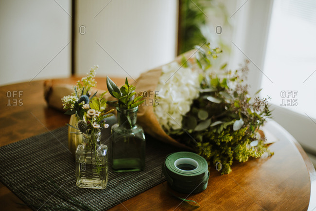 Flowers being arranged on a wooden table