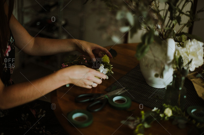 Florist arranging flowers on a wooden table