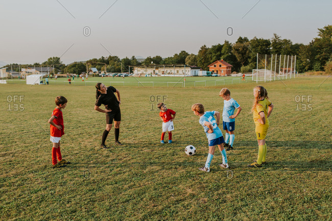 Children warming up before training. Group of kids stretching together with their female coach before soccer game in field at sunset.