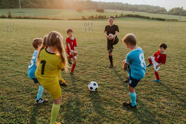 Children exercising with their coach outside. Group of kids stretching together with their female coach before soccer game in field at sunset.