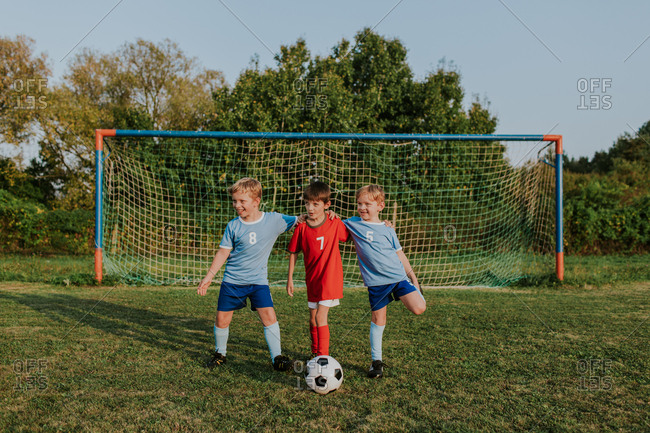 Children in front of football goal. Cheerful boys wearing soccer dresses having fun at amateur competition in field at sunset.