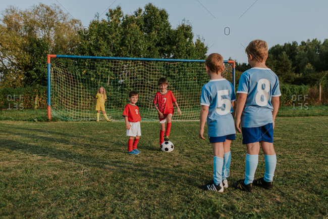 Children playing amateur football. Cheerful kids in teams wearing soccer dresses having fun playing soccer in field at sunset.