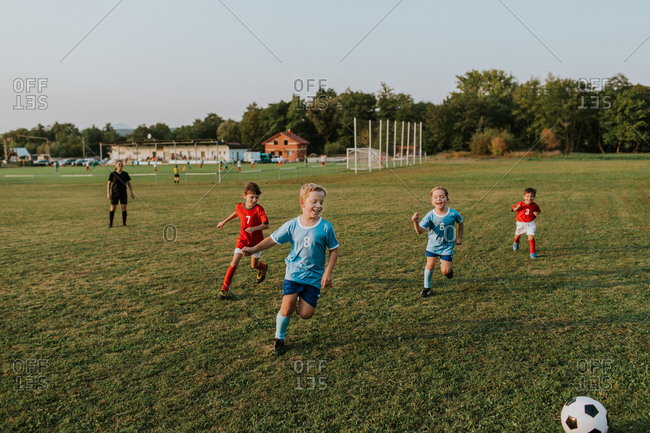 Children playing amateur soccer. Cheerful boys running after football ball outside on pitch at sunset.