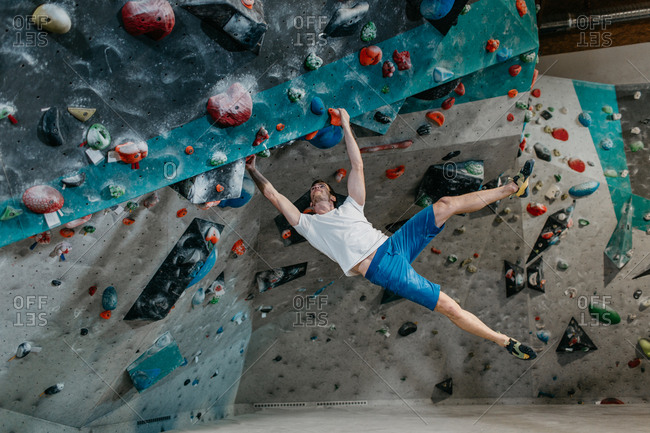 Male climber hanging from an artificial climbing wall in an indoor bouldering gym. Focused boulderer swinging at a bouldering wall.