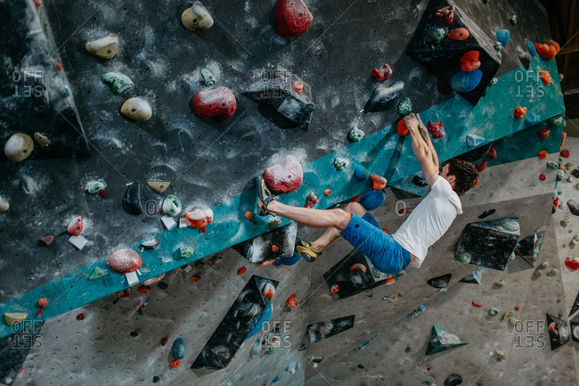 Male climber hanging from an artificial climbing wall in an indoor bouldering gym. Focused boulderer climbing up a bouldering wall.