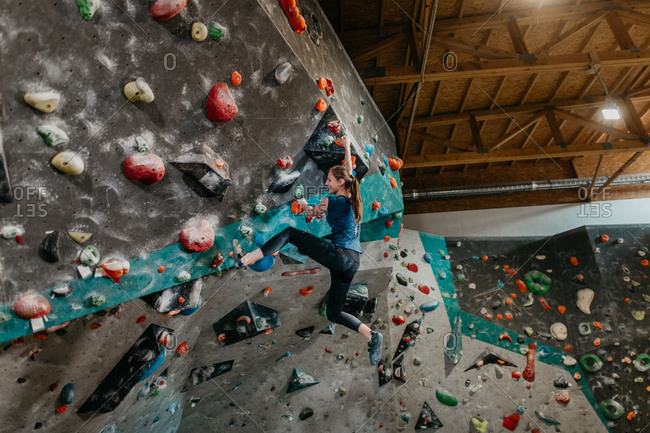 Side view of a woman climbing up an artificial climbing wall in an indoor bouldering gym. Cheerful female boulderer hanging from a bouldering wall.