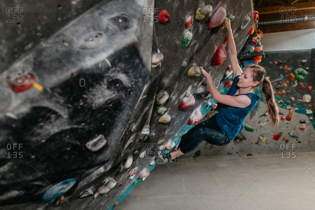 Side view of a woman hanging from an artificial climbing wall in an indoor bouldering gym. Female boulderer making her way up a bouldering wall.