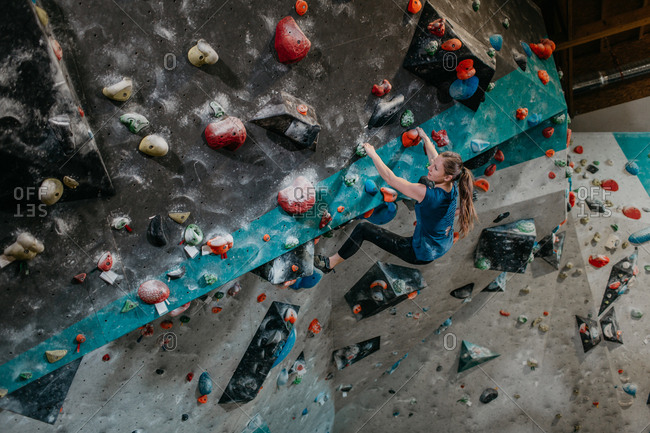 Woman climbing up an artificial climbing wall in an indoor bouldering gym. Female boulderer making her way up a bouldering wall.