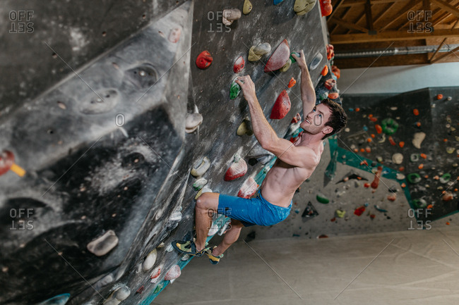 Side view of a man climbing up an artificial climbing wall in an indoor bouldering gym. Male boulderer making his way up a bouldering wall.