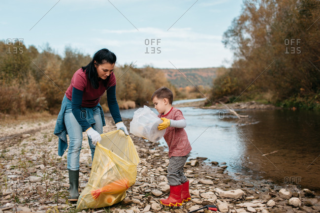 Female volunteer and her child collecting garbage on river beach. Toddler putting plastic waste in bag on the beach.
