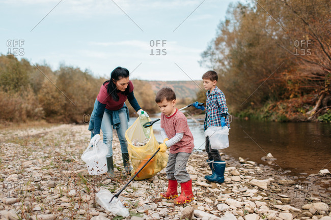 Toddler with trash picker picking up plastic bottle on the beach. Female volunteer and her children collecting garbage around river.
