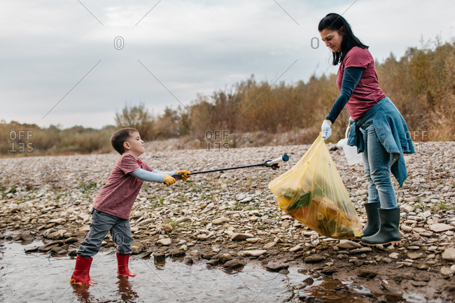 Child with trash picker standing in water putting empty plastic bottle in bag. Female volunteer and her toddler son collecting garbage from the river.