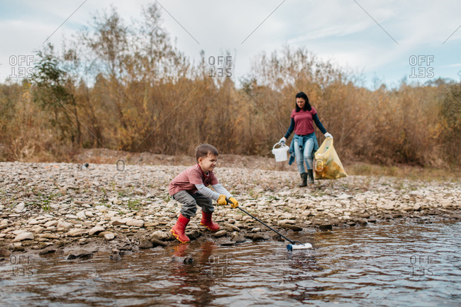Child with trash picker trying to reach plastic waste from the water. Female volunteer and her toddler son collecting garbage around river.