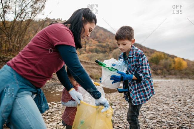 Young boy putting plastic waste in bag on the beach. Female volunteer and her children collecting garbage on river beach.