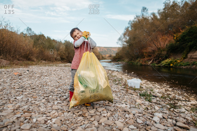 Front view of toddler boy carrying bag full of plastic waste around river beach. Portrait of child volunteer lifting up yellow plastic bag filled with rubbish.