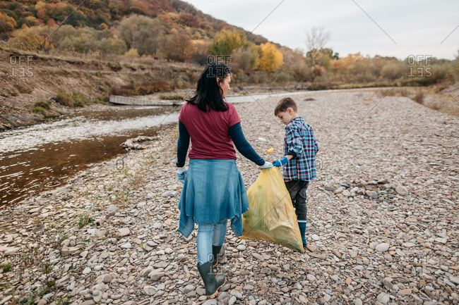 Back view of woman and her son walking along river beach collecting rubbish. Rear view of female volunteer and her child carrying plastic bag filled with garbage.