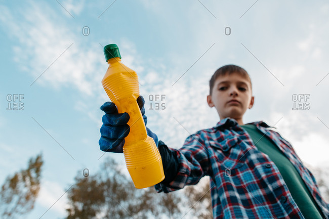 Low angle view of unfocused young boy wearing blue gloves holding plastic bottle against blue sky. Portrait of child showing empty plastic bottle into camera - focus on glove and bottle.
