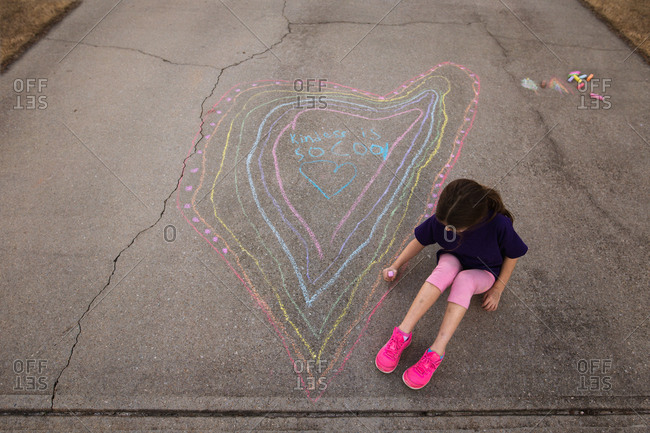 Little girl writing with chalk on her driveway