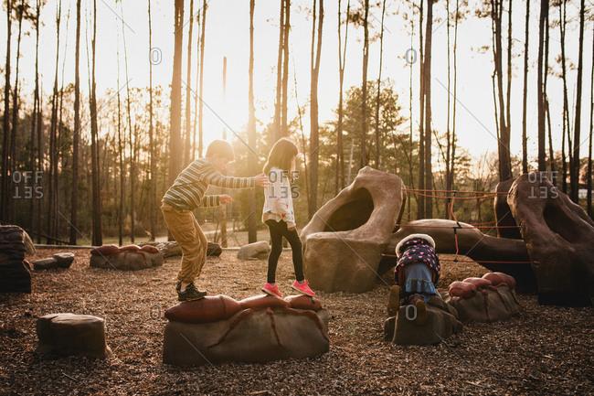 Three kids climbing at a playground