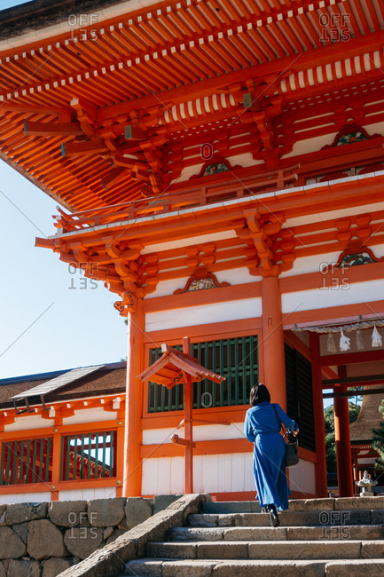 Person walking up the steps of a Japanese shrine
