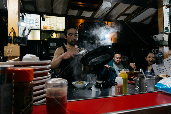 Fukuoka, Japan - November 28, 2018: Person preparing street food at a Japanese yatai food cart