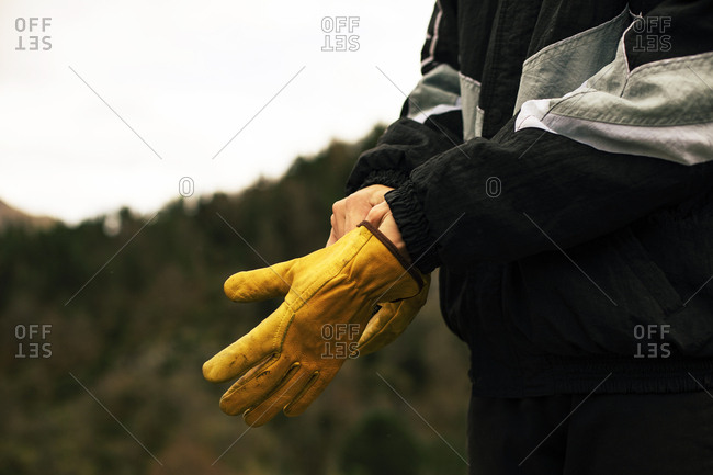 Close up of the hands of a unrecognizable man getting a yellow gloves