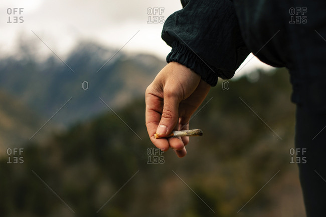 Close up of the hands of a unrecognizable man with a joint