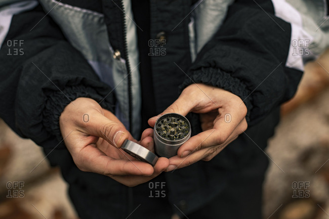 Close up of the hands of a man with a grinder and marijuana