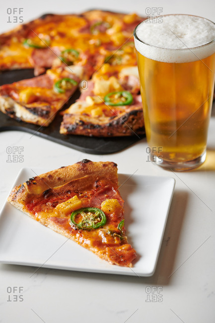 Slice of hawaiian pizza with pineapple and canadian bacon and sliced jalapeno on a square plate served with a pint of beer on a marble like table at a hip restaurant.