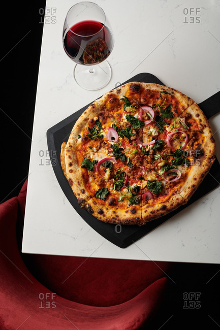 Sausage and Kale pizza with pickled red onions and micro greens made in a stone oven and served at a hip restaurant with a glass of red wine on a black pizza serving slab on a marble style table.