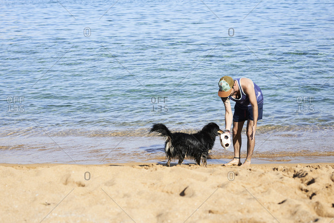Man and dog play with deflated ball at the beach in summer.