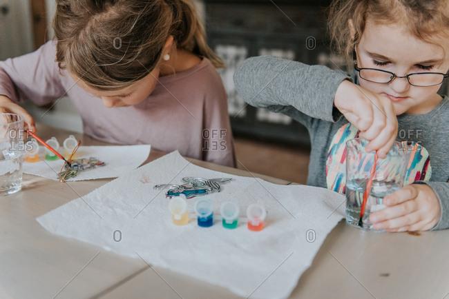 Two girls painting sun catchers