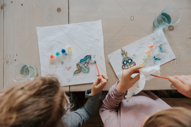 Overhead view of two girls painting sun catchers