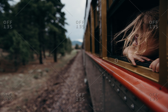 Young girl looking out train window