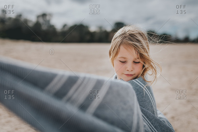 Young blonde girl wrapped in blanket on beach
