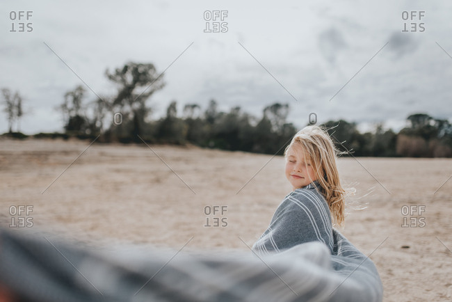 Young blonde girl dancing on a beach wrapped in a blanket