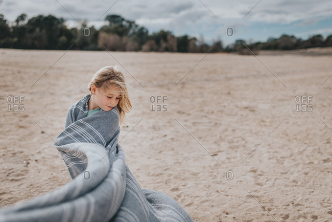Young blonde girl wrapped in blanket on a windy beach