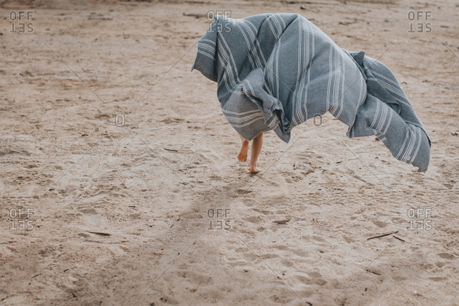 Child running with a blanket on a beach