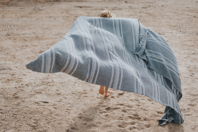 Young girl running with a blanket on a beach