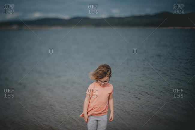 Young girl standing by lake on windy day