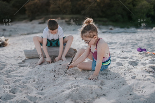Two kids playing in sand on a beach