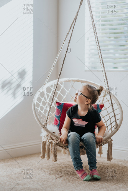 Little girl sitting in hanging chair indoors