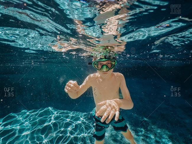 Boy wearing green goggles underwater in pool